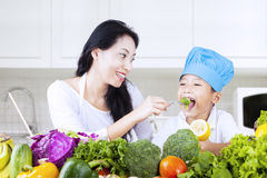 Happy boy eating broccoli with mom at home royalty free stock photo