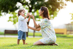 Beautiful mother gives child a drink of water in the park. Portrait of beautiful mother gives child a drink of water in the park Stock Image