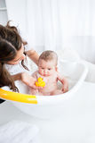 Beautiful mother giving the bath to her baby Stock Photos