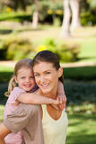 Beautiful mother giving daughter a piggyback Stock Image