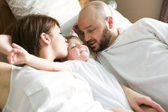 Beautiful mother and handsome father with baby daughter lying on bedroom. A beautiful mother and handsome father with baby daughter lying on bedroom Royalty Free Stock Images