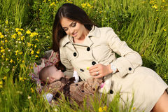 Beautiful mother having fun with her little cute baby in summer garden Royalty Free Stock Images