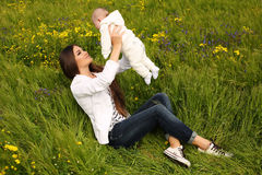 Beautiful mother having fun with her little cute baby in summer garden Royalty Free Stock Photo