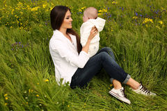 Beautiful mother having fun with her little cute baby in summer garden Stock Photos