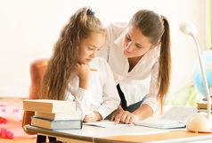 Beautiful mother helping daughter doing homework Stock Images