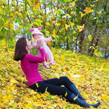 Beautiful mother and her baby in autumn park Stock Image
