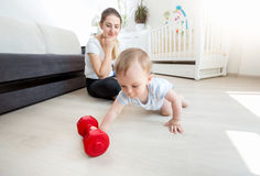 Beautiful mother with her baby boy exercising with dumbbells on Royalty Free Stock Photo
