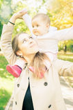 Beautiful mother with her baby girl outdoor at autumn park Royalty Free Stock Photography