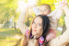 Beautiful mother with her baby girl outdoor at autumn park Royalty Free Stock Image