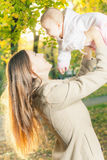 Beautiful mother with her baby girl outdoor at autumn park royalty free stock photos