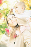 Beautiful mother with her baby girl outdoor at autumn park Royalty Free Stock Photo
