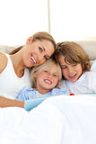 Beautiful mother and her children reading book. Lying in bed Royalty Free Stock Image