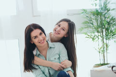 Beautiful mother and her cute daughter smiling and posing at home. Royalty Free Stock Images