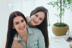 Beautiful mother and her cute daughter smiling and posing at home. stock photography