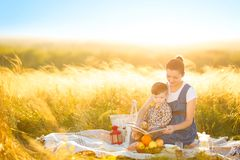 Beautiful mother and her cute son reading a book on a picnic on the sunset background. Happy family and education concept Stock Image