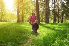 Beautiful mother and her cute son walking in the park. At sunny day Royalty Free Stock Images