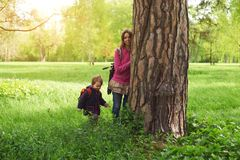 Beautiful mother and her cute son walking in the park. At sunny day Royalty Free Stock Photos