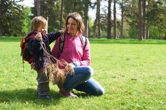 Beautiful mother and her cute son walking in the park. At sunny day Stock Image