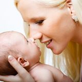 Beautiful mother with her daughter. Closeup faces of young happy mother with cute newborn baby royalty free stock photo