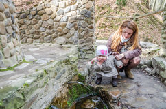 Beautiful mother with her daughter Baby drink water from the holy spring that flows from the rock among the vegetation. Beautiful mother with her daughter Baby stock image