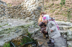 Beautiful mother with her daughter Baby drink water from the holy spring that flows from the rock among the vegetation. Beautiful mother with her daughter Baby royalty free stock photography