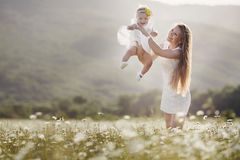 Beautiful mother and her daughter playing in spring flower field Royalty Free Stock Image