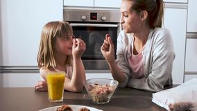 Beautiful mother and her daughter taking and eating cereals of bowl in the kitchen at home