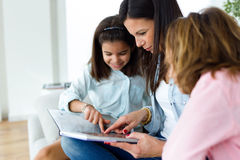 Beautiful mother with her daughters reading a book at home. Royalty Free Stock Image