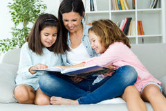 Beautiful mother with her daughters reading a book at home. Royalty Free Stock Images