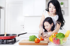 Beautiful mother and her girl cooking together Royalty Free Stock Images