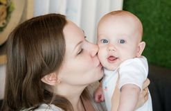 Mother kissing her son. Beautiful mother and her happy baby son portrait Stock Photos