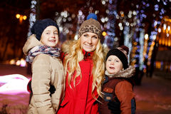 Beautiful mother with her kids. In new year on street at night Stock Image
