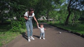 Beautiful Mother And her little son outdoors. Boy holding mother's hand. Portrait of cute kid making first steps