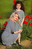 Beautiful mother with her little daughter in poppies green field Stock Photography