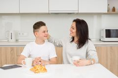 Happy family in the morning. Beautiful mother with her son having sitting at table in kitchen and having conversation, smiling and hugging. Family concept about Royalty Free Stock Photography