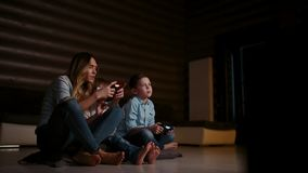 Beautiful mother with her son playing video games on gaming console in the living room of his house. Happy family in a stock video