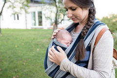 Beautiful mother with her son in sling, green nature Royalty Free Stock Images