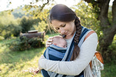 Beautiful mother with her son in sling, green nature Royalty Free Stock Image