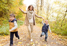 Beautiful mother with her sons in autumn forest. Royalty Free Stock Photo