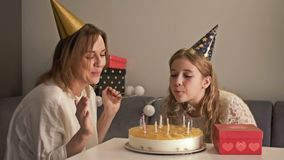 Beautiful mother and her teenager daughter are celebrating a birthday. Mom and child are blowing on candles on cake