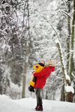 Beautiful mother and his son walking in winter park during snowfall royalty free stock photos