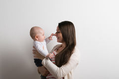 Beautiful mother holding baby son in her arms. Studio shot. Royalty Free Stock Images