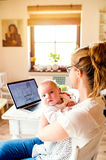 Beautiful mother holding baby son, laptop on table, close up. Close up of beautiful mother holding her baby son in the arms, laptop laid on table Stock Image