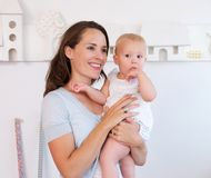 Beautiful mother holding cute baby indoors. Portrait of a beautiful mother holding cute baby indoors Royalty Free Stock Photos