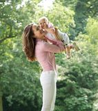 Beautiful mother holding cute baby in the park Royalty Free Stock Photography