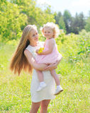 Beautiful mother holding on hands child with flowers in summer Stock Photography
