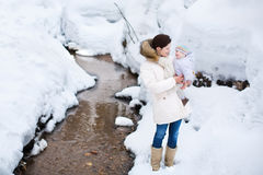 Beautiful mother holding her baby in snowy park Stock Image