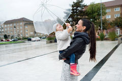 Beautiful mother holding her little daughter under the umbrella. Royalty Free Stock Photography