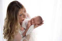 Mother Holding her Newborn Baby Daughter stock photos