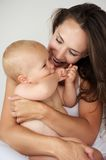 Beautiful mother hugging baby laughing together Stock Photos